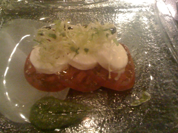 "Course One: Heirloom tomatoes with fresh mozzarella cheese. The swab of pesto on the side of plate added color and a wonderful flavor. Two of my favorite words are ""heirloom"" and ""tomato"""