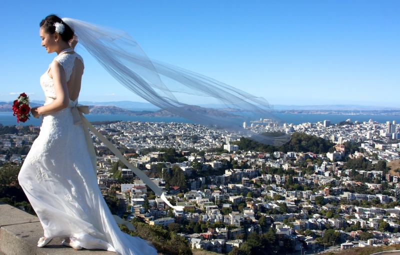 A bride poses for photos at the top of Twin Peaks in San Francisco